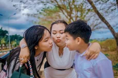 three person kissing near tree